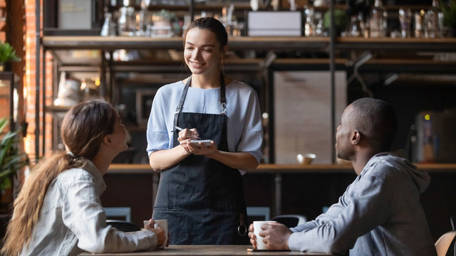 Smiling waitress taking order from multiracial clients