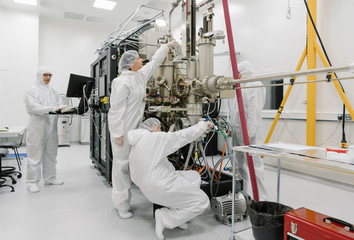 Laboratory technicians working on a device in laboratory of science center