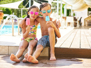Portrait of little girl and boy with popsicles wearing mirrored sunglasses in front of swimming pool
