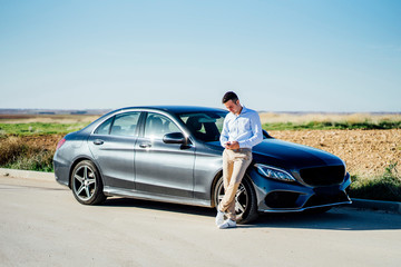 Young businessman leaning against car on country road using smartphone