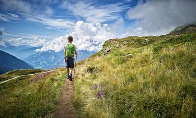 Boy hiking on footpath against cloudy sky Fotobehang
