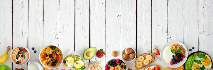 Healthy breakfast food banner with bottom border. Table scene with fruit, yogurt, smoothie bowl,...
