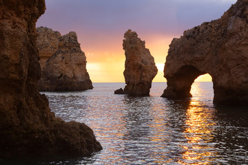 Portugal, Faro District, Lagos, Natural arch and coastal rock formations at dawn
