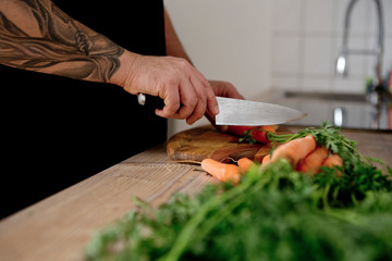 Close-up of tattooed man cutting carrots in kitchen