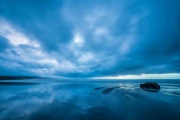New Zealand, Tongaporutu, Cloudy sky over sandy coastal beach at blue dusk