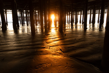 USA, California, Santa Monica, Setting sun illuminating beach sand under Santa Monica Pier