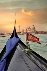 Wall Murals Gondolas gondola with a venetian flag in the stern floats along the lagoon at sunset