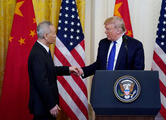 Chinese Vice Premier Liu He reaches out to U.S. President Donald Trump during U.S.-China trade signing ceremony at the White House in Washington