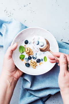 Hands holding a healthy breakfast bowl with yoghurt
