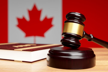 Close-up of the judge's hammer on a wooden table against the background of the Canadian flag, The concept of canadian legislation.3D rendering. - fototapety na wymiar