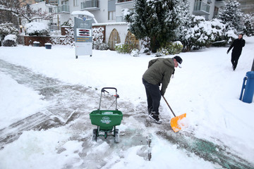 A man shovels the sidewalk outside his apartment building in Vancouver's West End after a snow storm in downtown Vancouver