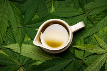 Cannabis oil on marijuana leaves covered table