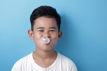 Cute Asian boy eating bubble gum and blow balloon