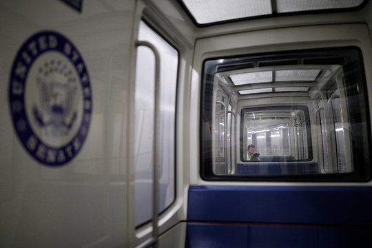 A person looks at a tablet device while riding on the Senate Subway ahead of a House vote on a resolution appointing managers for Senate impeachment trial against U.S. President Donald Trump in Washington