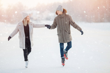 Loving couple in winter with skates on rink on sunset background, guy and girl dressed in warm hat