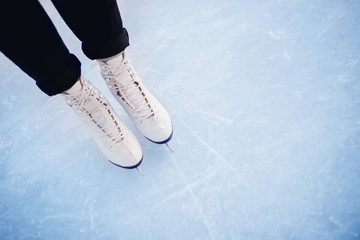Woman standing on ice in white figure skates, snow flakes sunset. Top view