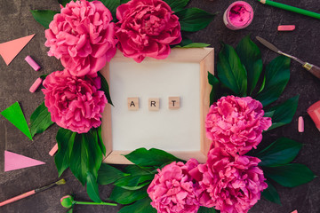 Compostion of ART word typing on wooden blocks on white card in photo frame, pink peony flowers with green leaves surrounded by variety of drawing supplies. Craft Art therapy. Creative working place.