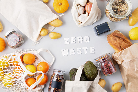 Zero Waste food shopping and storage in cotton eco bags. Glass jars with grains, reusable bags with fresh vegetables, fruits. Sustainable, ethical, plastic free lifestyle. Top view, flat lay