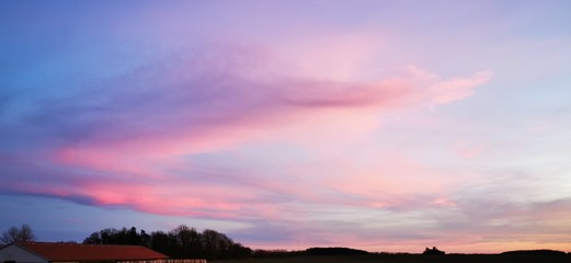 Foto auf Leinwand Rosa hell A fantastic sunset with red yellow orange and purple tones with dramatic cloud formation over green meadows with bare trees in January on the island of Rügen