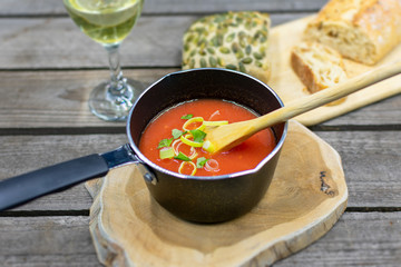 Homemade tomato soup in a pot with a wooden spoon.