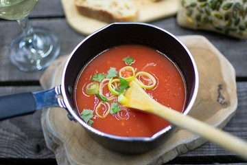 Hearty tomato soup in a saucepan with spring onions and herbs. Rustic arranged