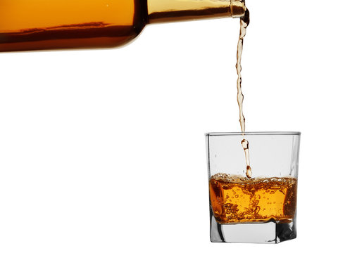 Whiskey or brandy from a bottle is poured into a glass. Isolated on a white background