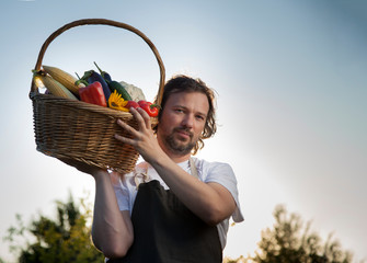 Farmer with an ecological harvest of vegetables in a basket near the garden beds in summer