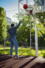 boys playing basketball outdoors on a sports field