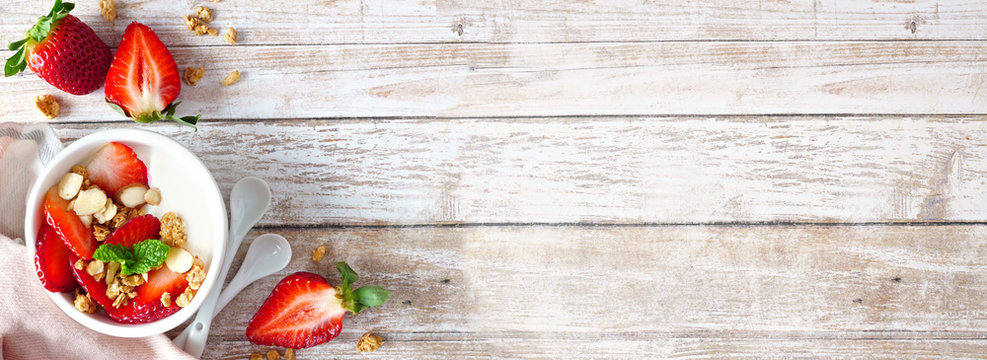 Healthy yogurt with fresh strawberries and granola. Banner with corner border against a rustic wood background. Copy space.