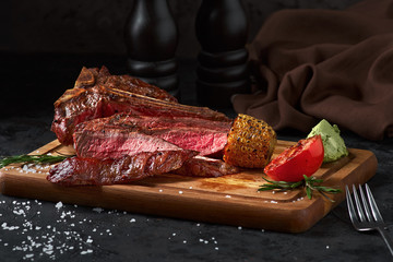 Close up sliced medium rare grilled beef steak with corn and tomato, pepper and rosemary on meat cutting board on dark wooden background
