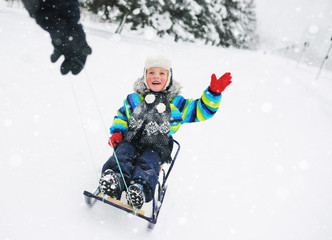 the hand of an adult pulls a small child boy on a sled in the snow. Winter entertainment