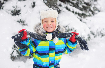 a child-a small cute boy in a winter jacket and hat ties a scarf against the background of snow and trees and smiles. Winter mood