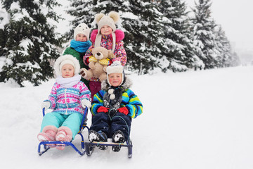 a group of children in colorful warm winter clothes on a sled with a Teddy bear on a background of snow and Christmas trees.