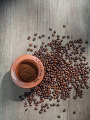 Black coffee ground in a clay mortar and in grains on the surface of a wooden table in sunny rays, with place for text. Top view.