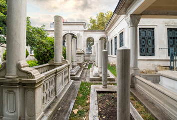 Historic interior courtyard of the Ahmet Tevfik Paşa Tomb filled with marbled headstones, graves and memorials to Turkey's rulers and sultans.