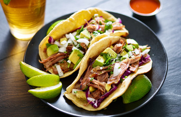 Wall Mural - pork carnita tacos close up with lime wedges and red cabbage