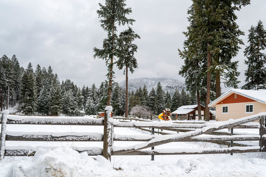 A winter scene of a country ranch home and barn covered in snow in the mountains of North Idaho, USA