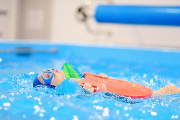 Little boy with glasses and inflatable armbands in swimming pool.