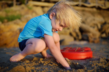 Little boy playing on sand beach near seashore in Greece