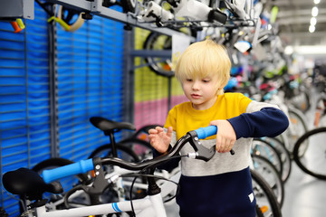 Little boy choosing bicycle in sport store.