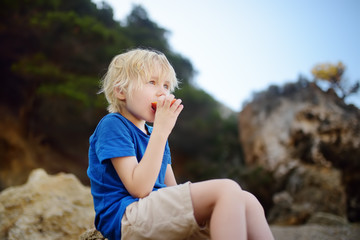 Little boy is eating peach during walking. Nature lover.