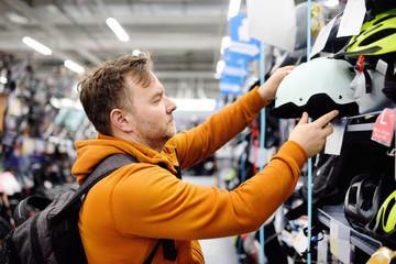 Middle age man choosing bicycle helmet in sport store.