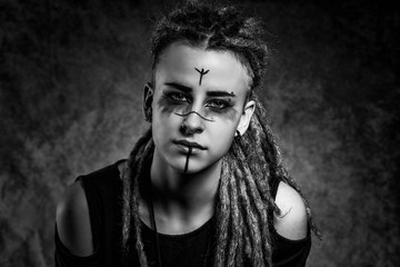 Black and white portrait of a stylish young woman with dreadlocks against dark background