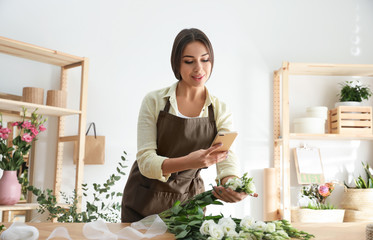 Florist taking picture of beautiful flowers in workshop