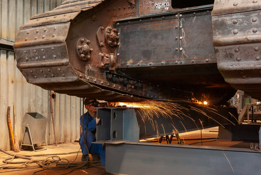 A worker performs grinding work on a old armored tank in a factory workshop.