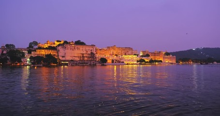 Wall Mural - Udaipur City Palace and Lal ghat on bank of lake Pichola with water ripples - Rajput architecture of Mewar dynasty rulers of Rajasthan. Sunset at Udaipur, India.