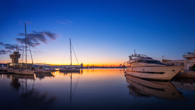Yacht port and beautiful sunset over Varna, Bulgaria. Sailboat harbor, many beautiful moored sail yachts in the sea