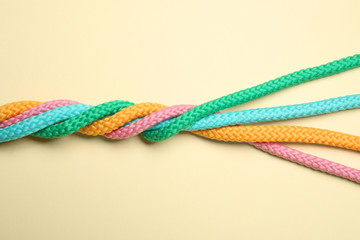 Twisted colorful ropes on beige background, top view. Unity concept