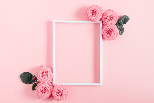 Beautiful flowers composition. Blank frame for text, pink rose flowers on pastel pink background. Valentines Day, Easter, Birthday, Happy Women's Day, Mother's day. Flat lay, top view, copy space