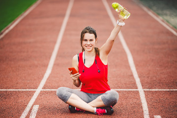 beautiful fitness girl uses smartphone at stadium after workout. Sports and healthy. Sport woman...
